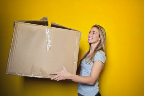 Woman moving a cardboard box in front of a yellow wall.