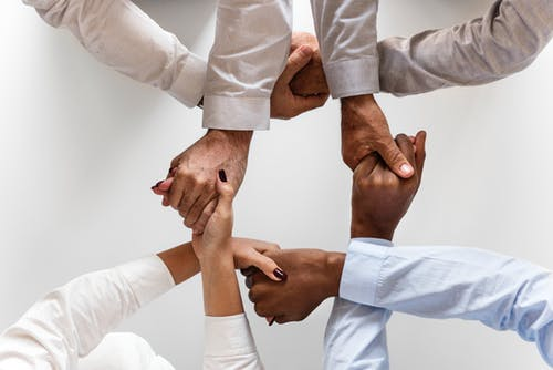 Coworkers holding hands to demonstrate how things can be stronger when you work together.