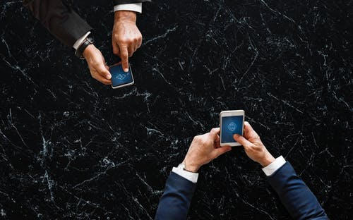 Two professionally dressed men securely sharing files online through cell phones.